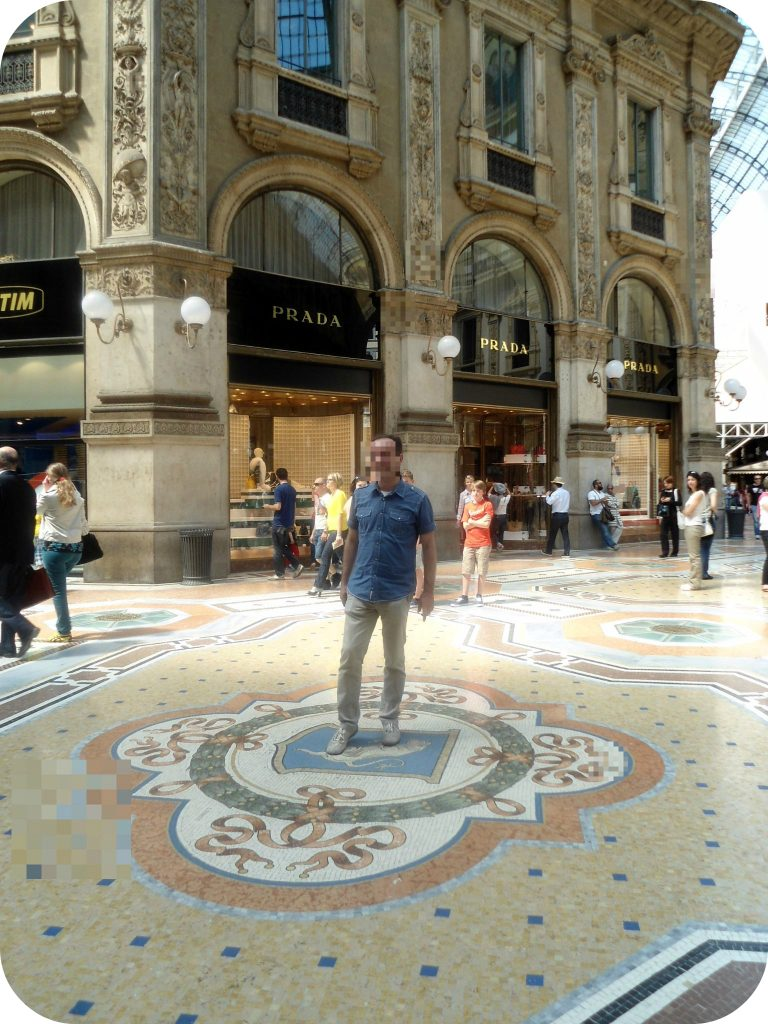 Man spinning in bull hole in Galleria Vittorio Emanuele in Milan